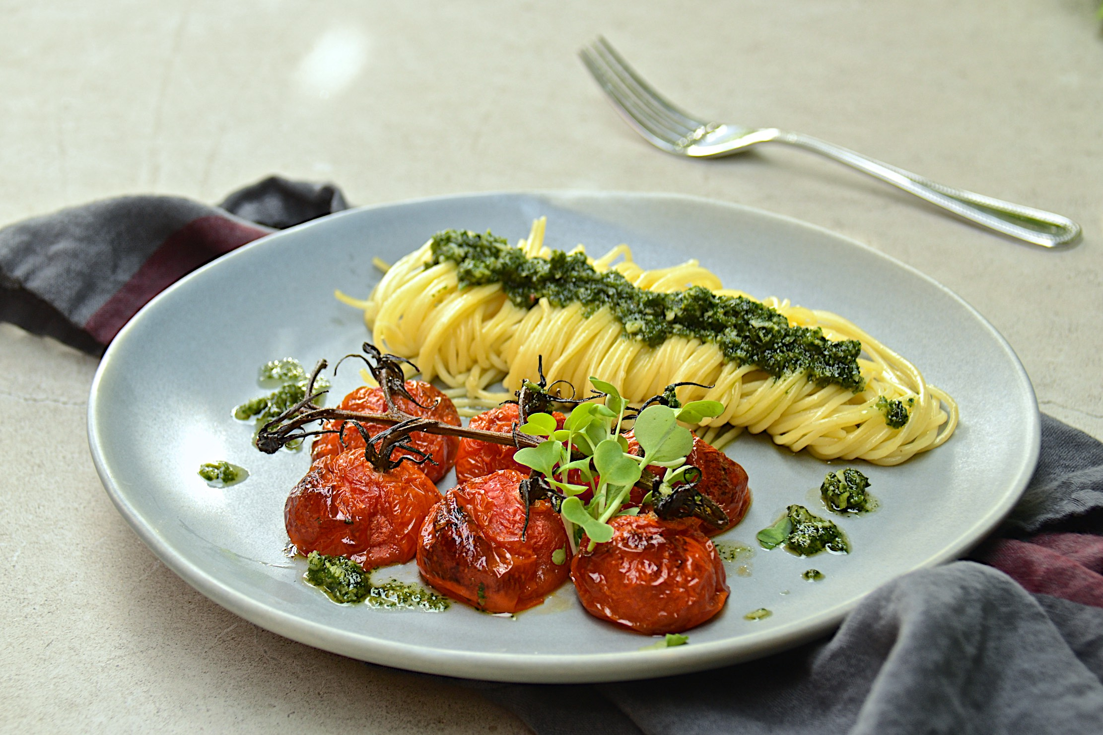 Pasta with pesto and roasted tomatoes on the vine